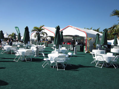 Large outside event with white tables and chairs